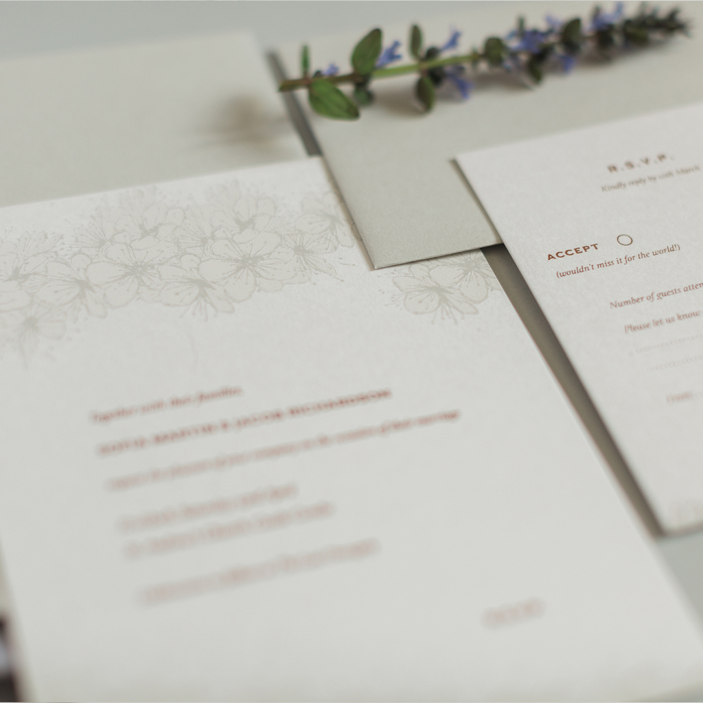 Image focused on the detailing of a botanical print wedding invitation. A cluster of hedgerow blossom along the top of the invitation is printed in a fine art style. By Inkflower Press
