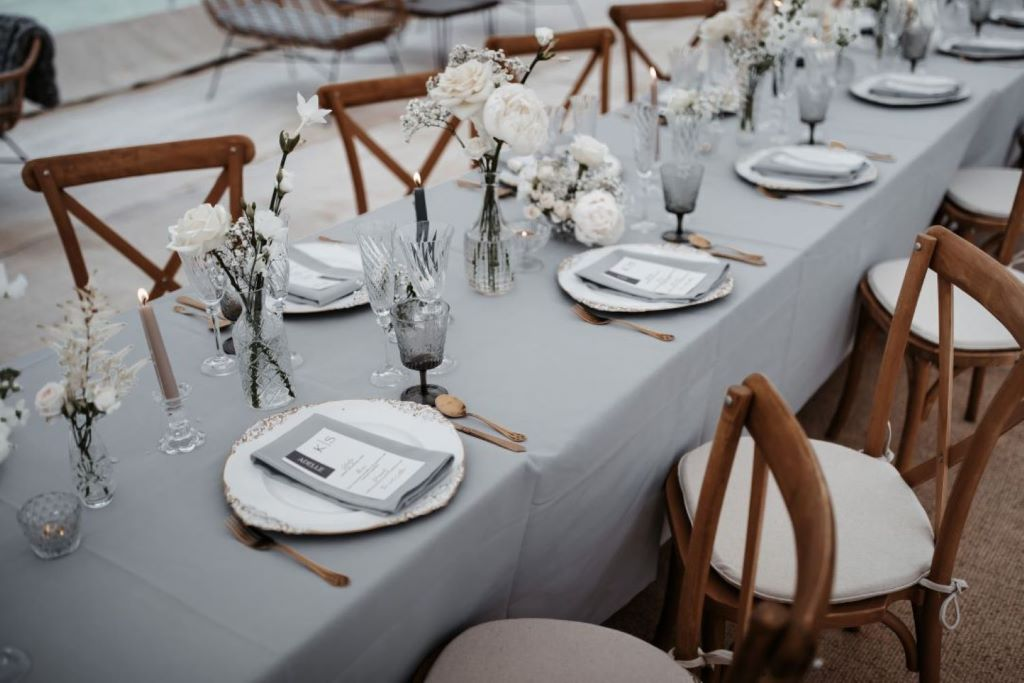 Styled wedding photoshoot with Wonderful Events on English Wedding. A bride and groom wearing black tie and white dress with all white flowers and grey tableware with smoky glass