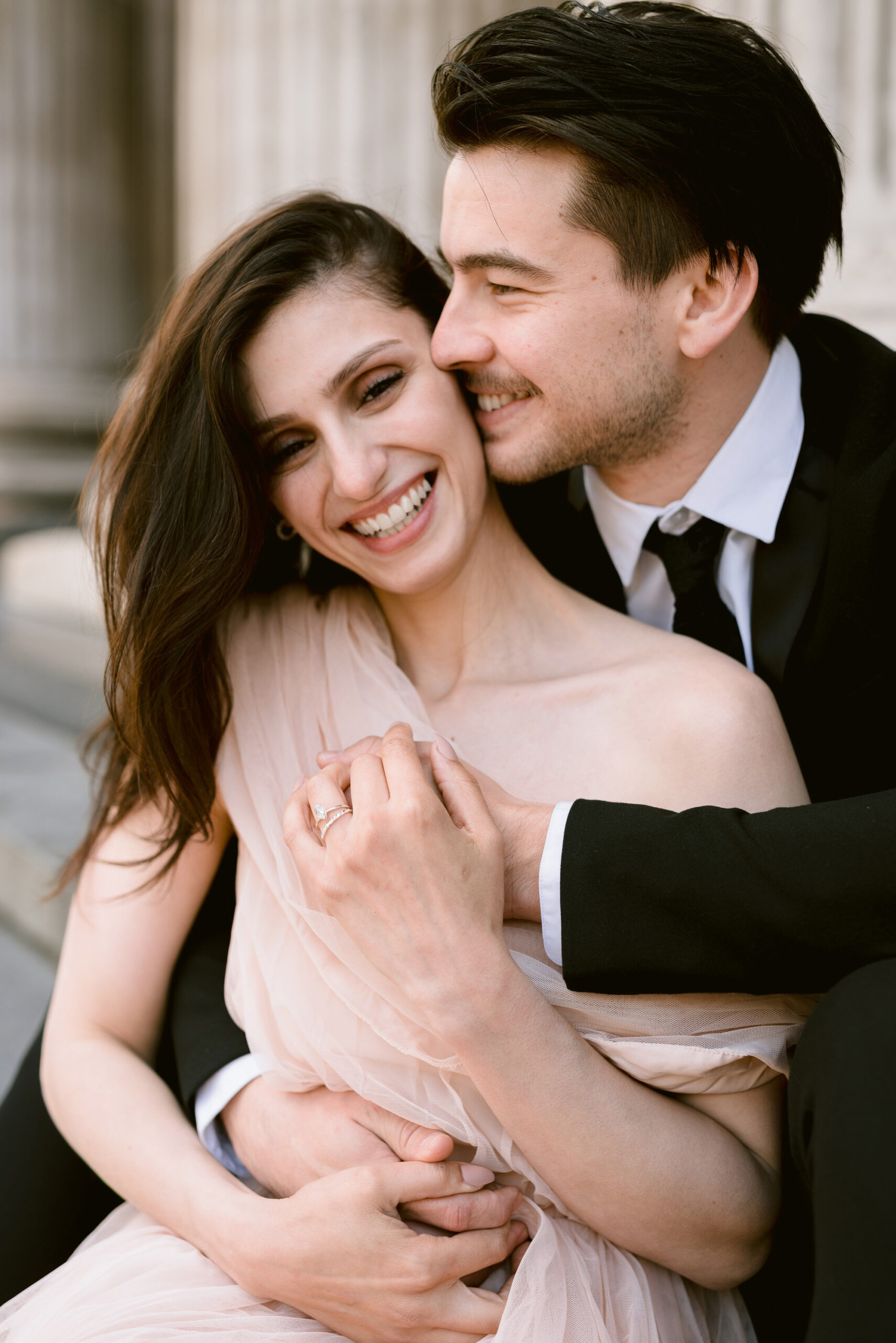 Katia and John photographed by St Paul's Cathedral in London. She wears a pale coral longline off the shoulder dress. He's in black tie and suit. Captured by Eva Tarnok Photography