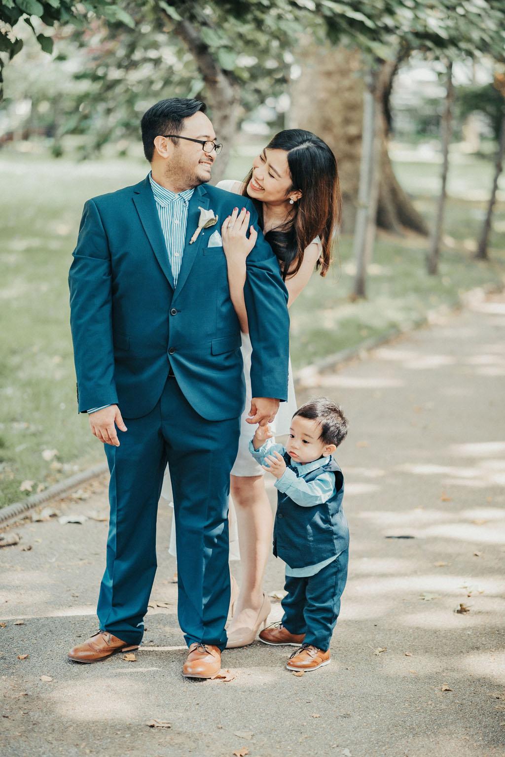 London rooftop micro wedding, Roanne wears a knee length white dress with asymmetrical skirt, Rey wears a blue suit