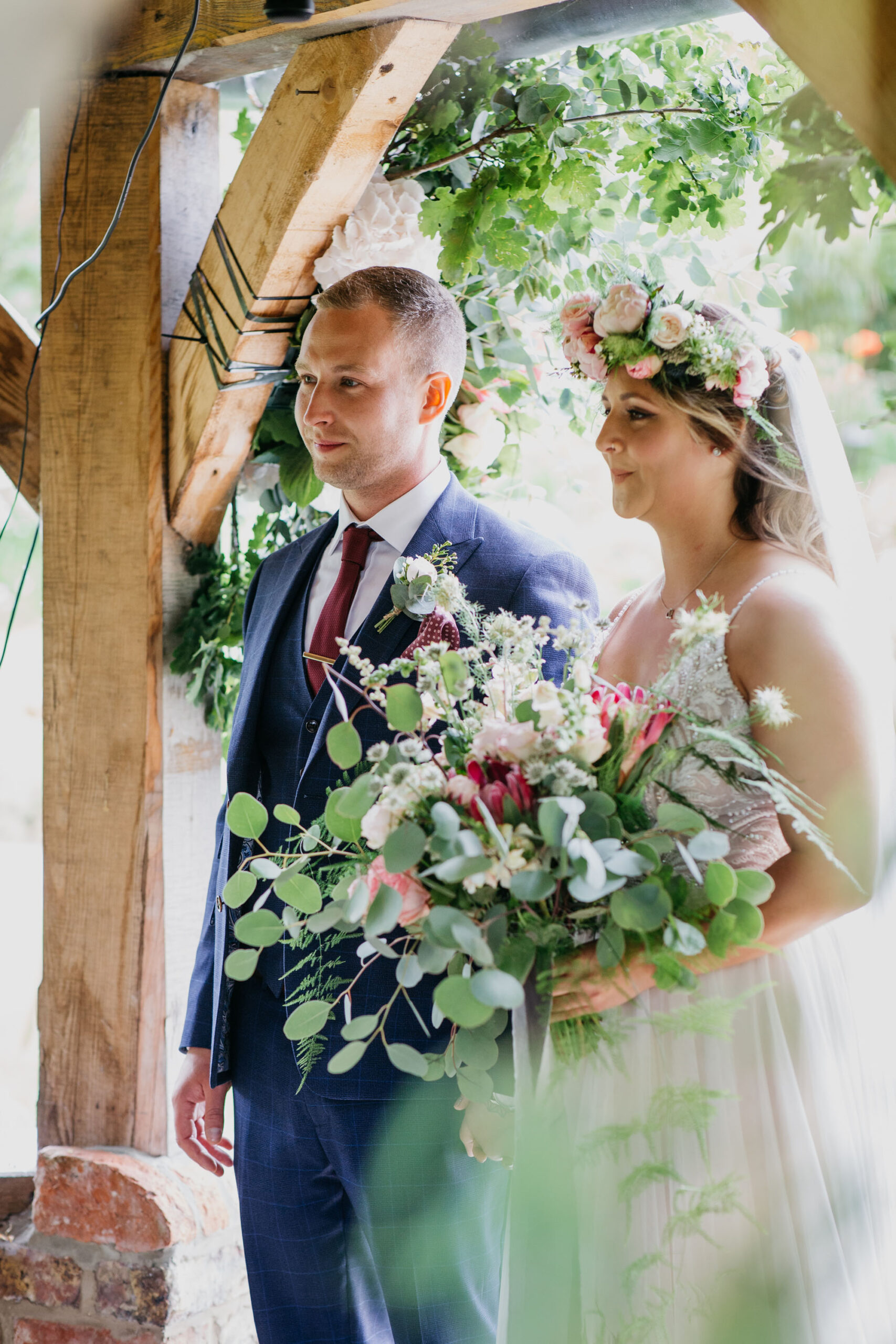 Yorkshire wedding photography of Alicia and Phil. She wears a white boho style dress and he's in a blue ckech suit. She has a full flower crown in delicate pinks, and they look happy. Image by John Hope Photography