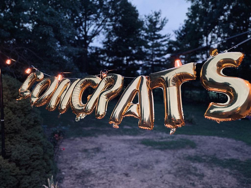A string of gold letter balloons spell Congrats. Image by Brett Garwood on Unsplash