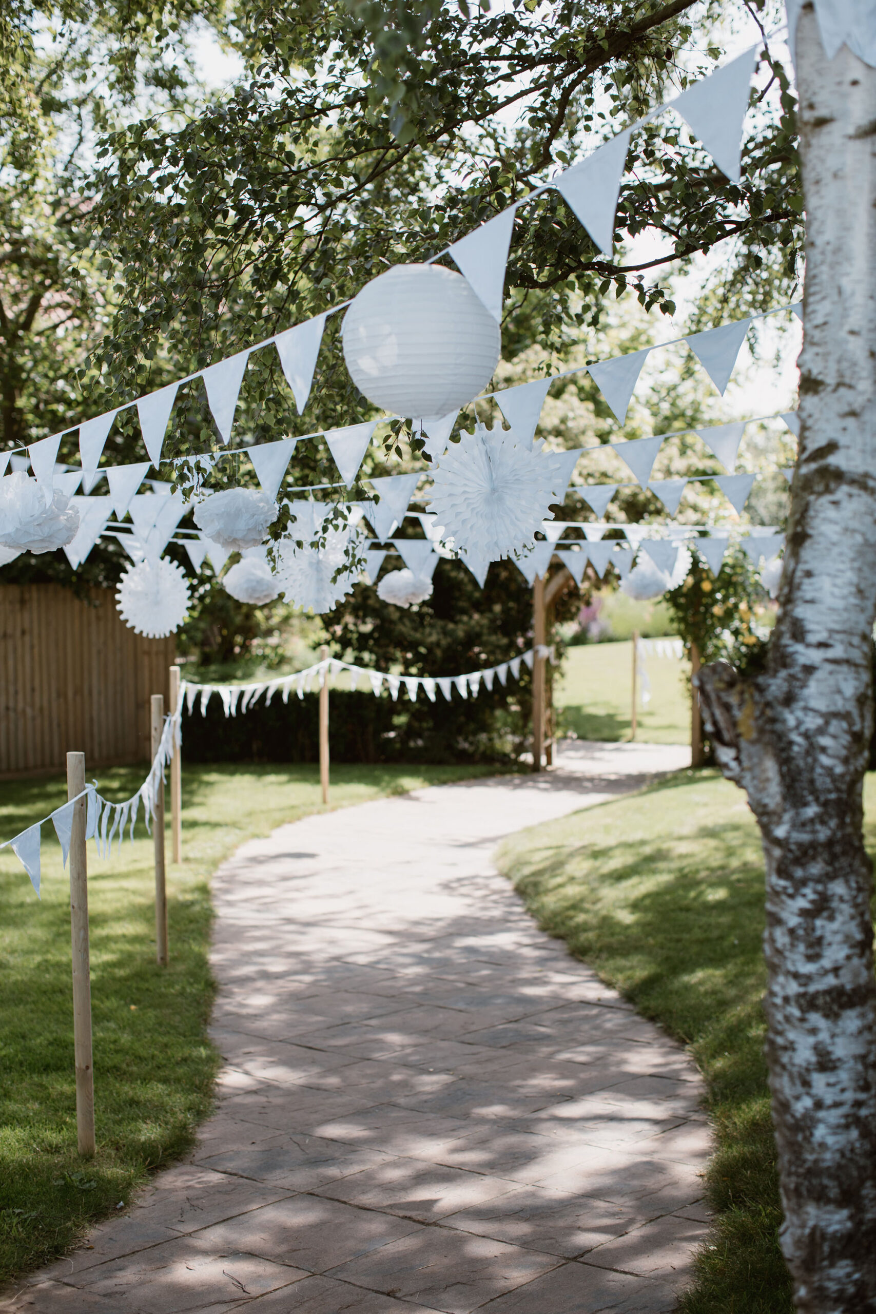A garden pathway is decorated with bunting and balloons in white tied from trees. Wedding image by Luke Hayden Photography