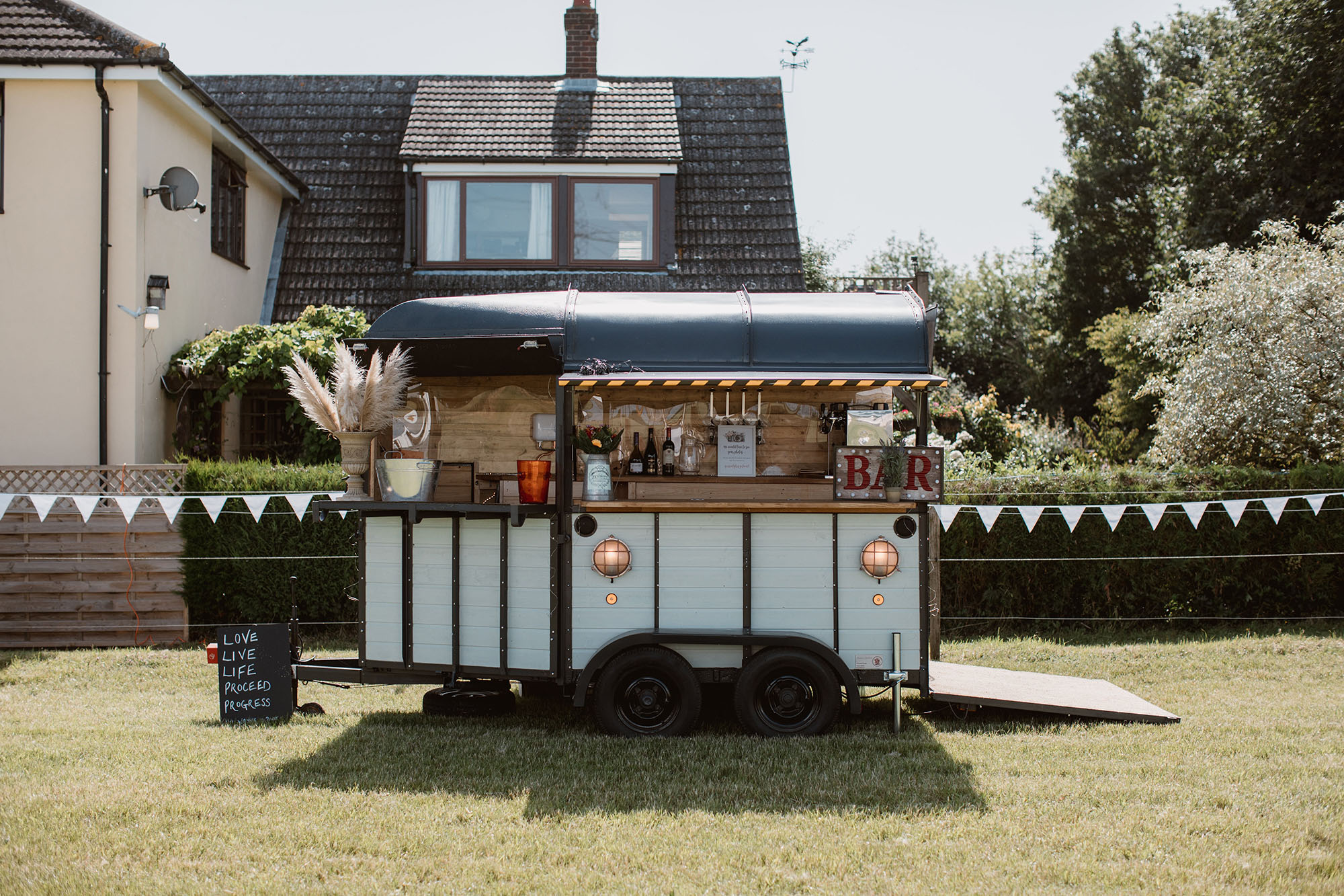 Mobile bar set up in a back garden. There's a house behind, white bunting and pampas grass on the end of the bar. Wedding image by Luke Hayden Photography