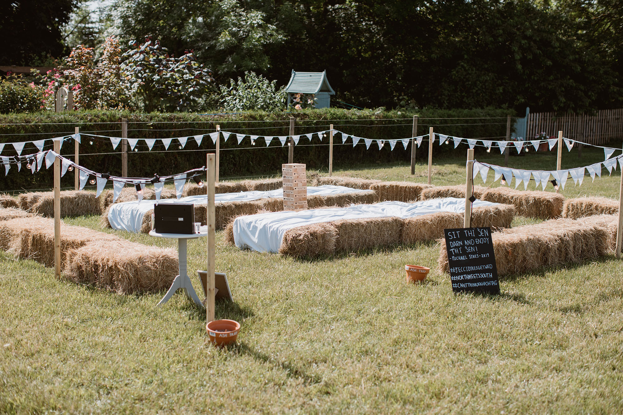A garden set out for wedding seating with hay bales and white bunting, with a sign about sitting down in a Yorkshire dialect! Wedding image by Luke Hayden Photography