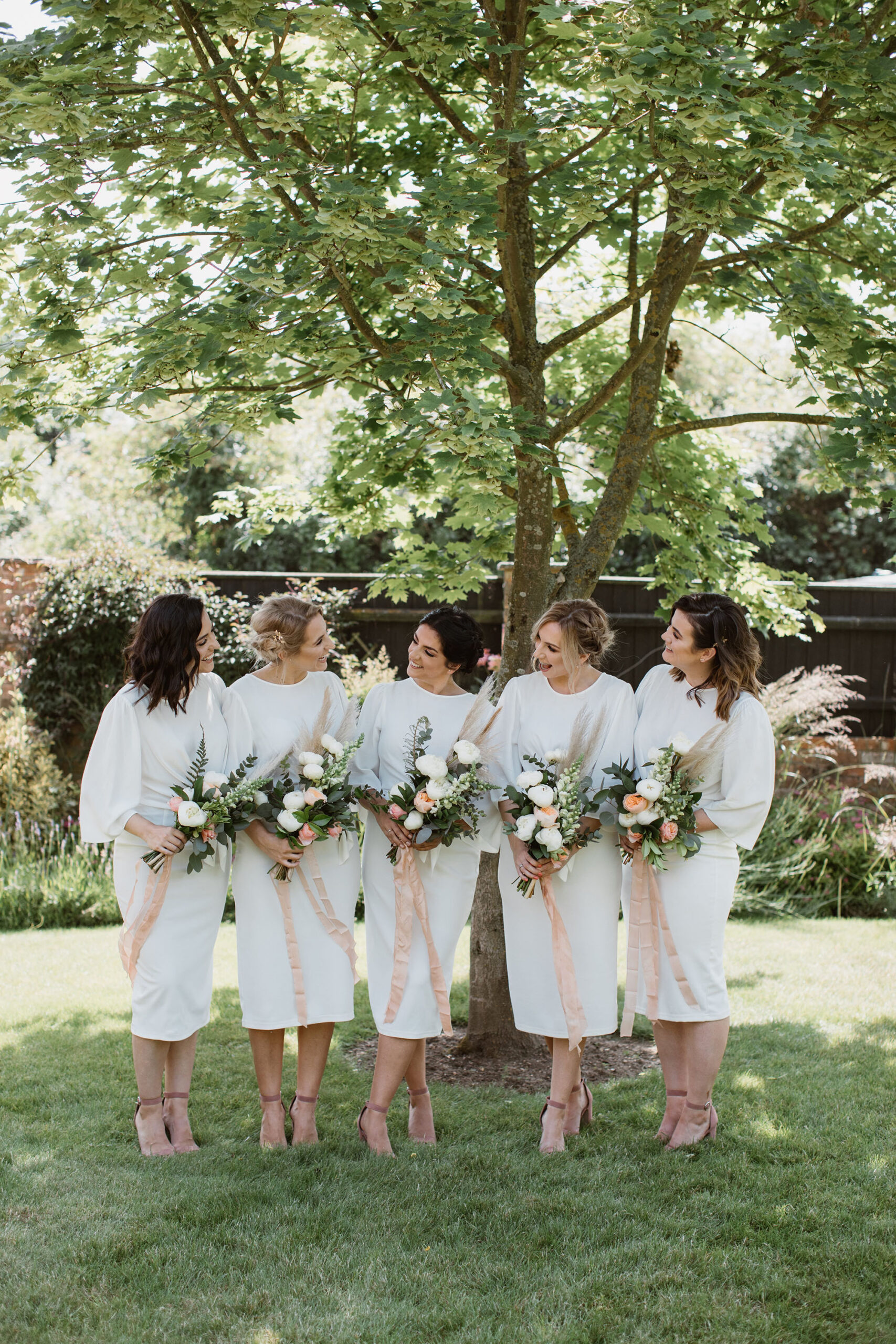 5 bridesmaids with simple white dresses and matching bouquets of white and peach flowers. They're standing in a garden in a line, talking and laughing. Wedding image by Luke Hayden Photography
