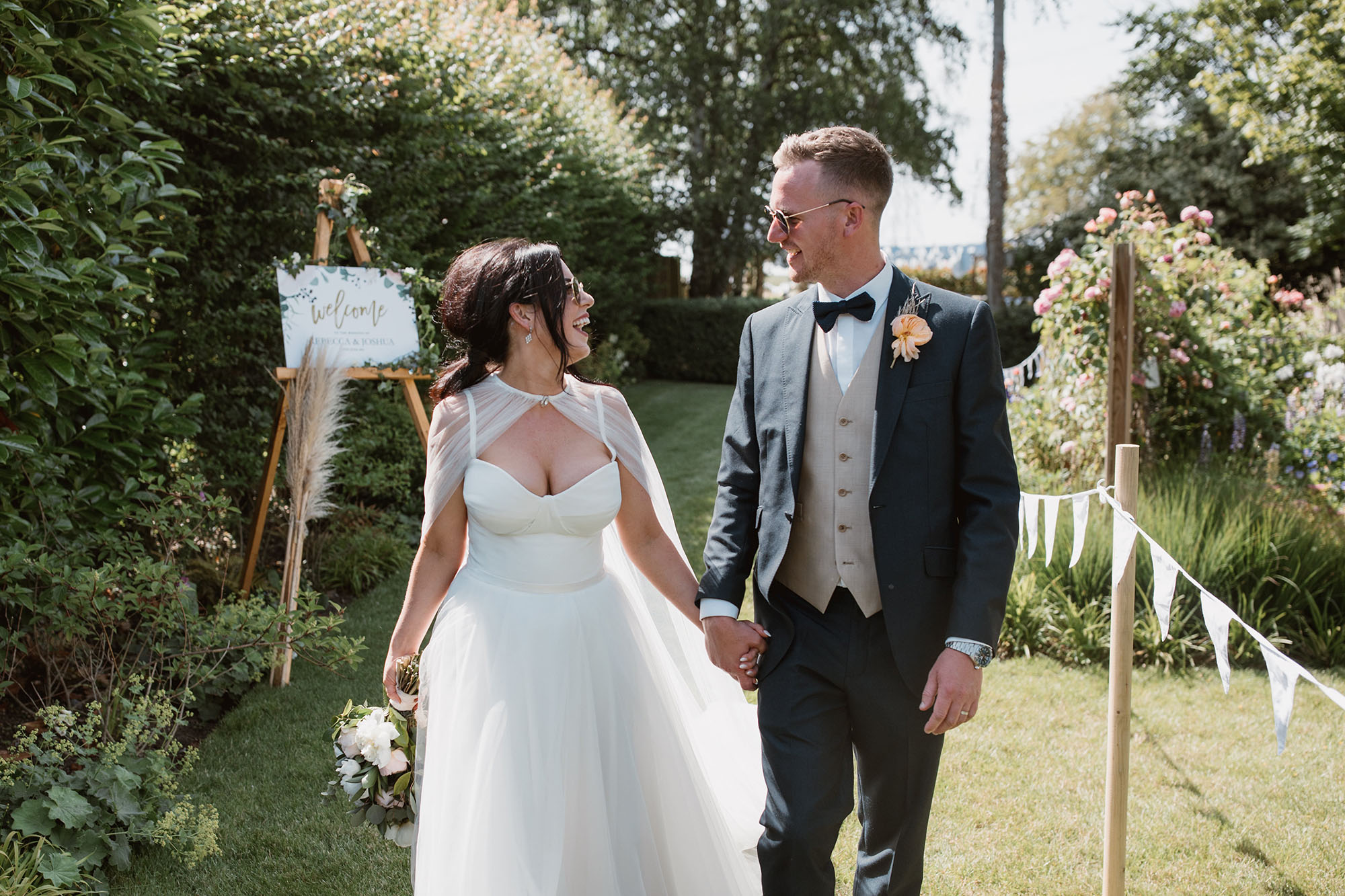 A bride and groom walk hand in hand in a garden. There's a welcome sign behind them. She's wearing a white scrappy dress and sheer cape. He's in a dark grey suit with bowtie. Wedding image by Luke Hayden Photography