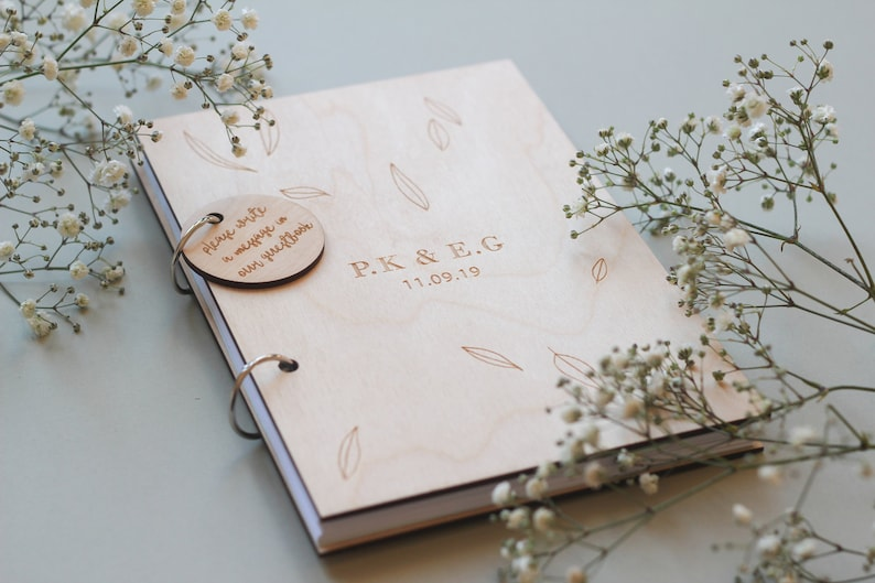 Pretty wooden wedding guest book with a circular tag and metal ring binding, by firastudio on Etsy