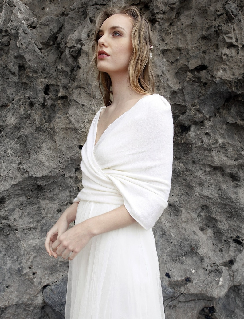 A model wears a beautiful white wool wedding shawl wrapped around her shoulders and tied at the back. She's stood in front of a grey rock