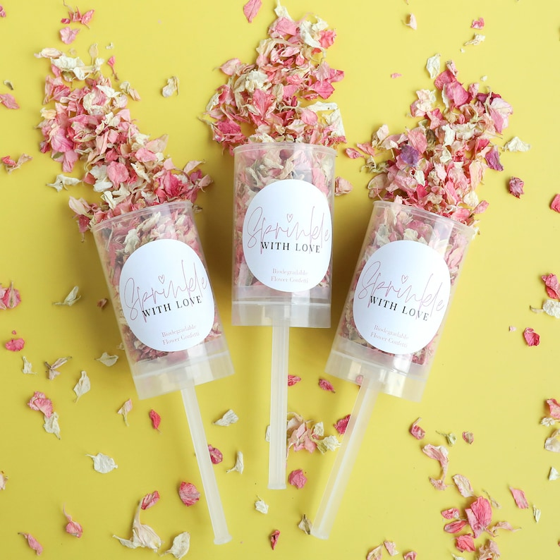 3 open Confetti Push Pops with dried pink petals on a yellow background, with labels saying Sprinkle with Love