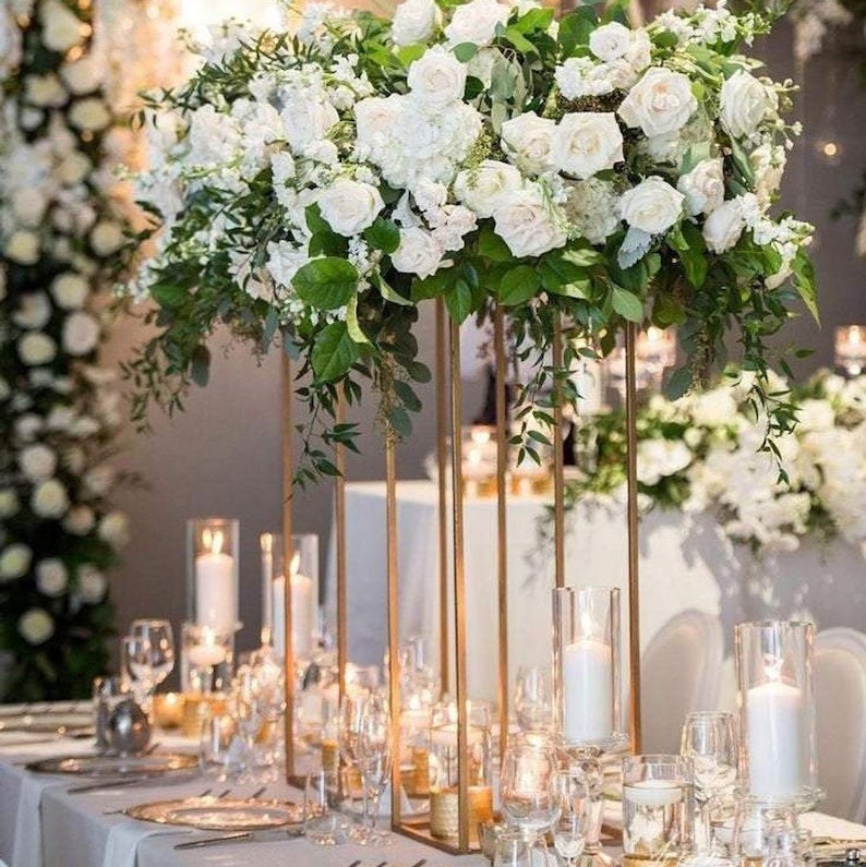 A white floral arrangement of roses and leaves sits on top of gold candle lanterns on wedding tables, surrounded by lit candles