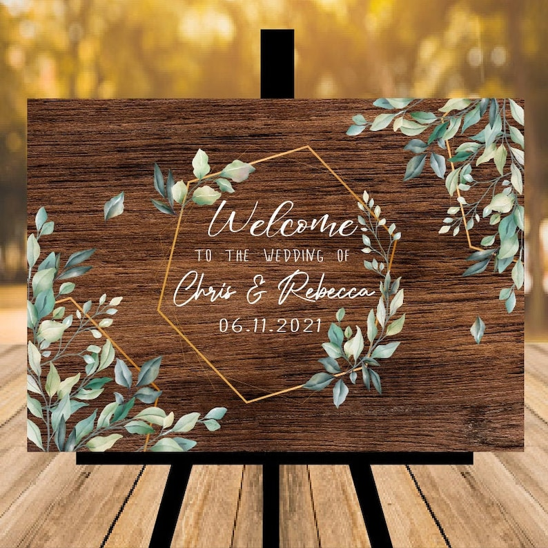 Dark walnut wedding sign printed with leaves in shades of blue green, with a hexagon and welcome text in the centre, by Wood Supplies on Etsy
